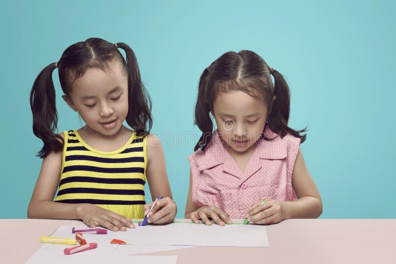 Un bambino creativo di due asiatici con il pastello che attinge lo scrittorio fotografie stock