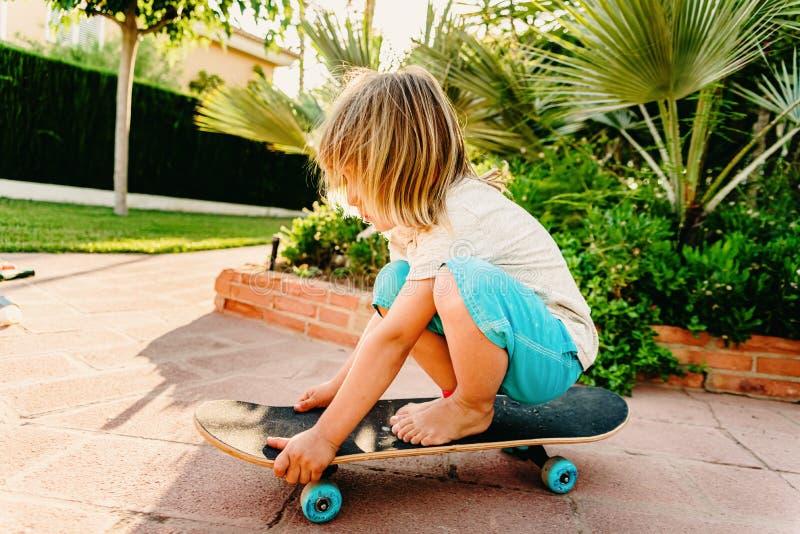 Un bambino di 5 anni che pratica pattini nel suo giardino temendo di cadere fotografia stock