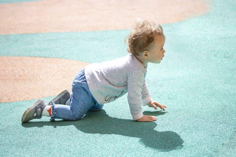 Un bambino di 1 anno striscia intorno al campo da giuoco Il bambino è vestito in jeans, in maglioni e negli stivali del denim immagini stock