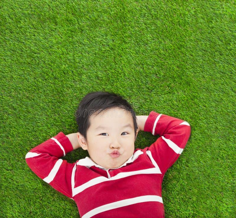 Un bambino di espressione di parodia che si trova e che tiene la sua testa immagini stock