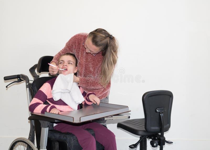 Un bambino disabile in una sedia a rotelle insieme ad un lavoratore volontario di cura immagine stock libera da diritti
