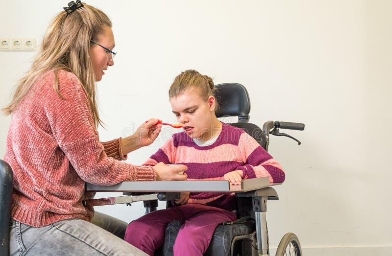 Un bambino disabile in una sedia a rotelle insieme ad un lavoratore volontario di cura fotografia stock