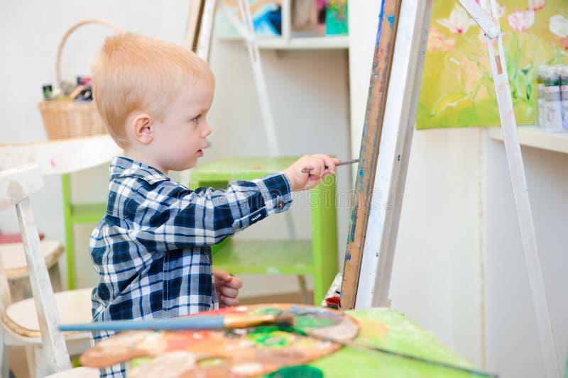 Un bambino disegna un'immagine dipinge sulla lezione di arte fotografia stock libera da diritti