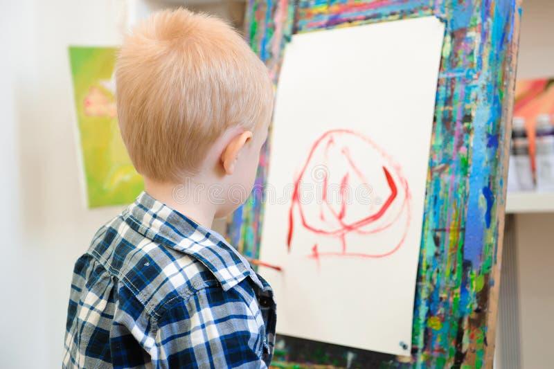 Un bambino disegna un'immagine dipinge sulla lezione di arte fotografie stock