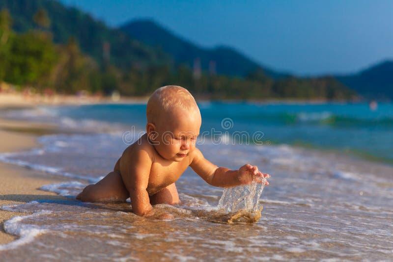 Un bambino divertendosi su una spiaggia tropicale fotografia stock