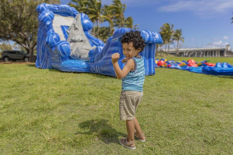 Un bambino fa il suo ballo felice mentre guarda una casa di rimbalzo gonfiare immagine stock libera da diritti
