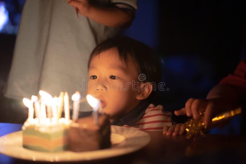 Un bambino felice sta soffiando le candele sulla sua torta di compleanno alla sua notte della festa di compleanno fotografia stock libera da diritti