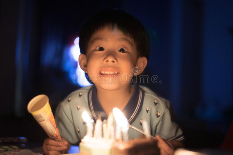 Un bambino felice sta soffiando le candele sulla sua torta di compleanno alla sua notte della festa di compleanno immagine stock
