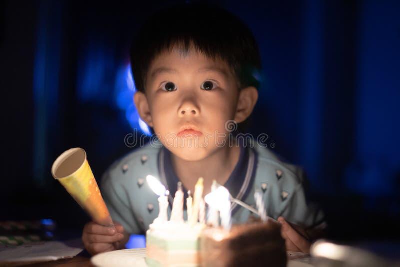 Un bambino felice sta soffiando le candele sulla sua torta di compleanno alla sua notte della festa di compleanno fotografia stock