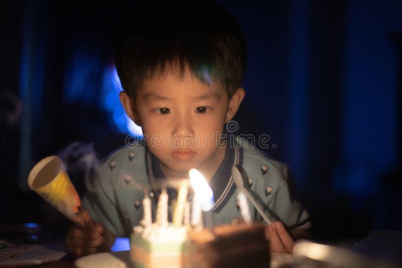 Un bambino felice sta soffiando le candele sulla sua torta di compleanno alla sua notte della festa di compleanno fotografie stock