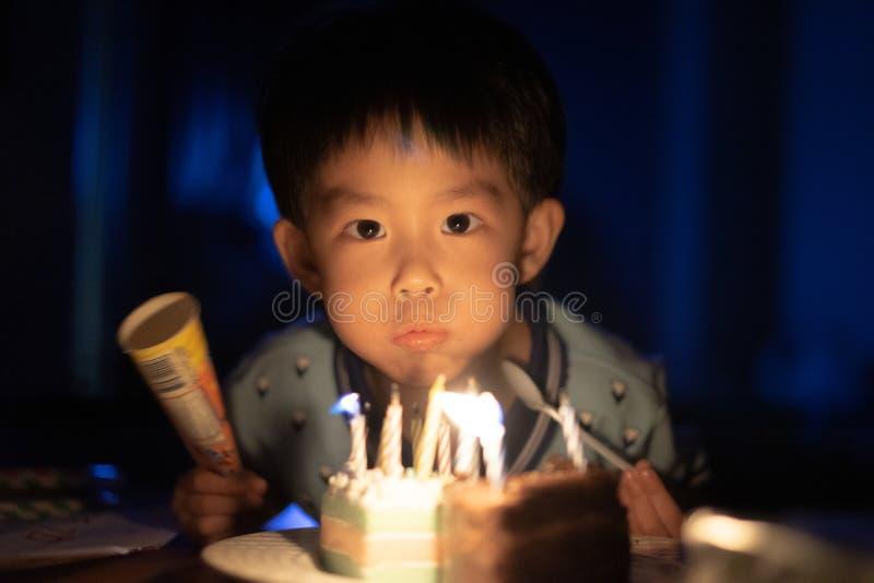 Un bambino felice sta soffiando le candele sulla sua torta di compleanno alla sua notte della festa di compleanno immagini stock
