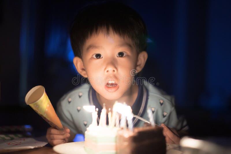 Un bambino felice sta soffiando le candele sulla sua torta di compleanno alla sua notte della festa di compleanno immagine stock libera da diritti