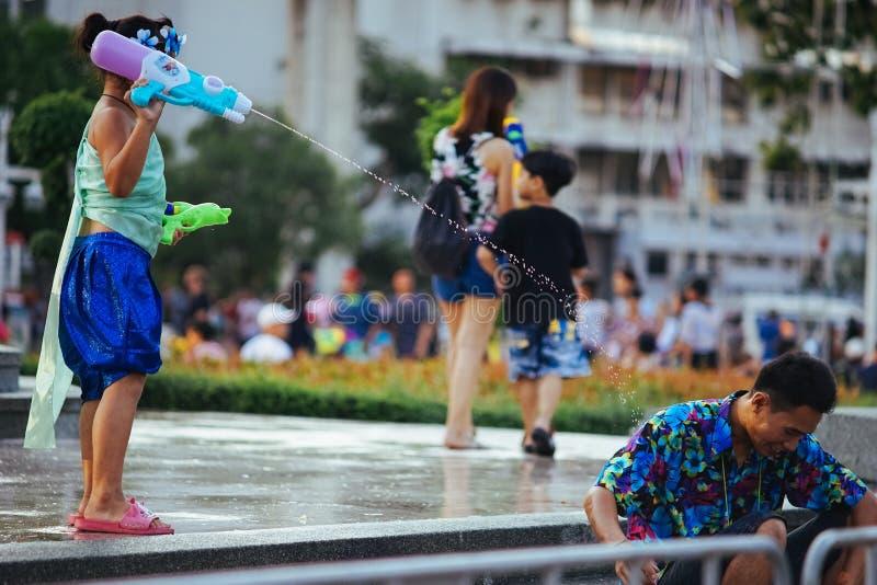 Un bambino gioca l'acqua con suo padre durante il Songkran fotografia stock