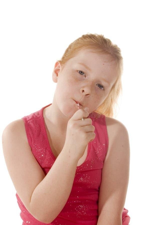 Un bambino in giovane età gode di un lollypop fotografie stock libere da diritti