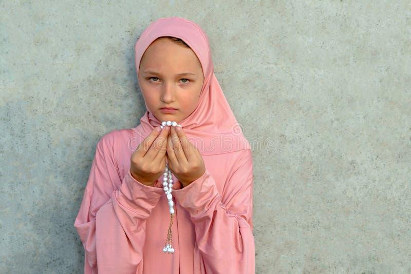 Un bambino in un hijab rosa con perle in sue mani con lo spazio della copia Concetto religioso di stile di vita della gente fotografia stock