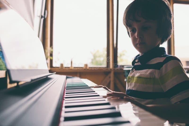 Un bambino impara giocare il piano fotografie stock