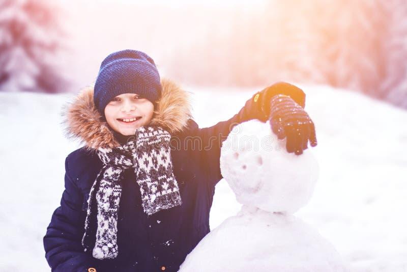 Un bambino scolpisce un pupazzo di neve immagini stock libere da diritti