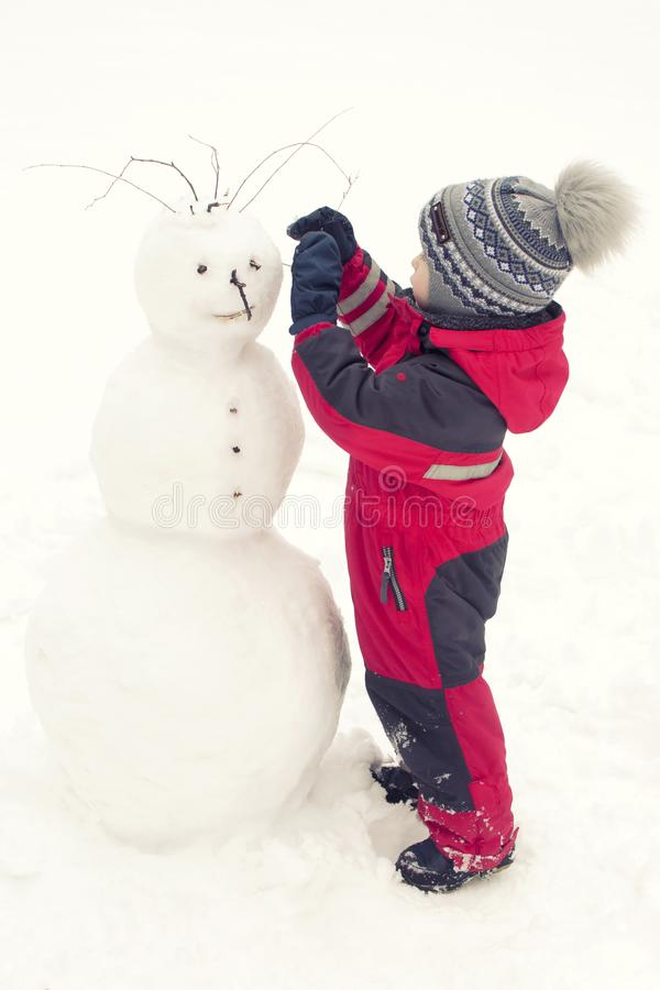 Un bambino scolpisce un pupazzo di neve nell'inverno sulla via, un ragazzo in un rosso complessivo fotografie stock libere da diritti