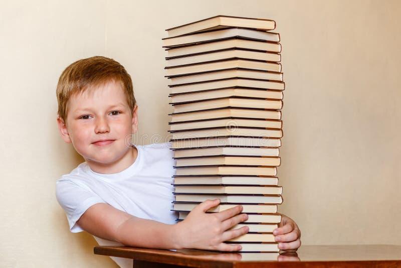 Un bambino sorridente di otto anni e una grande pila di libri bambini e lettura fotografie stock
