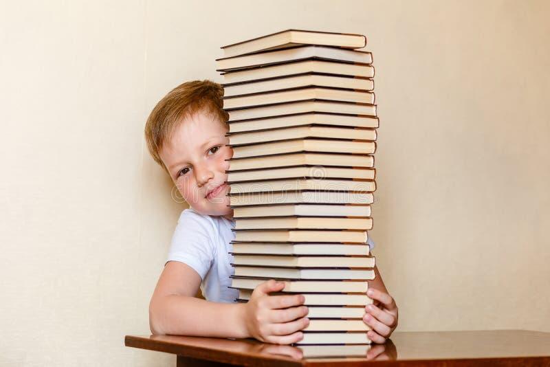 Un bambino sorridente di otto anni guarda fuori da dietro una grande pila di libri bambini e lettura fotografia stock libera da diritti