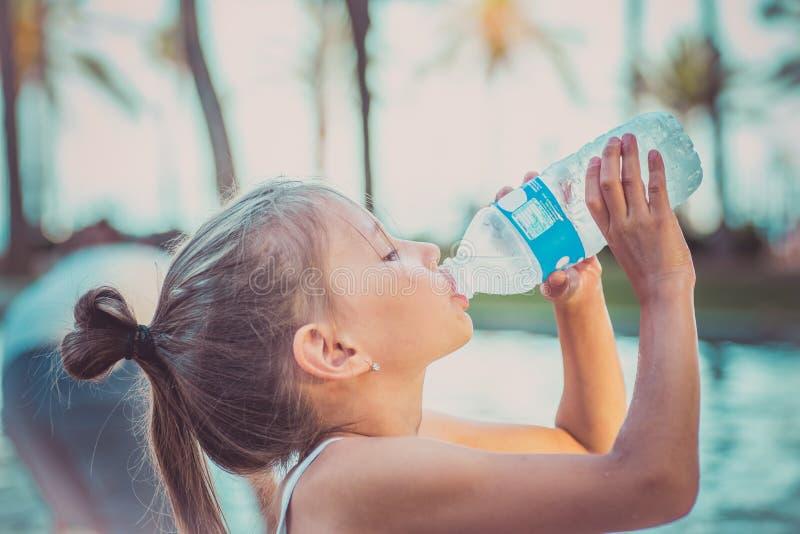 Un bambino sta bevendo l'acqua pulita da una bottiglia Giorno di estate caldo fotografie stock