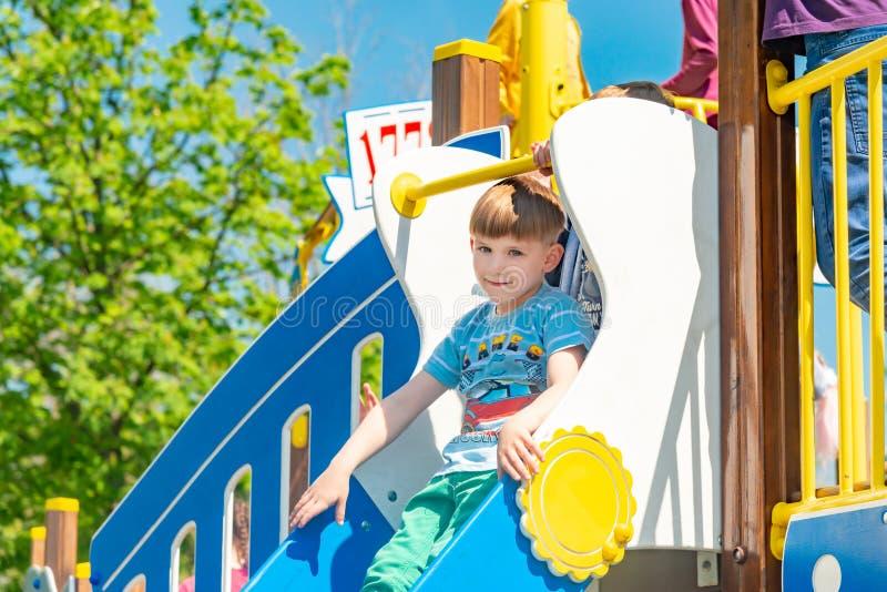Un bambino su un campo da giuoco di sport sta guidando su una collina, divertendosi durante le vacanze estive fotografie stock libere da diritti