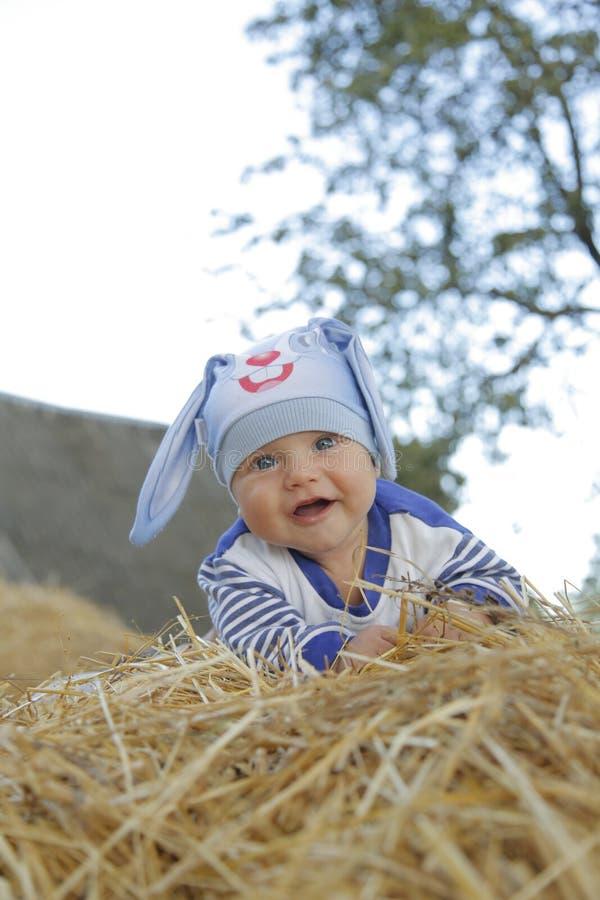 Un bambino sveglio in un vestito del coniglietto si trova sulla paglia immagini stock libere da diritti