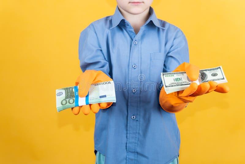 Un bambino in una camicia blu e nei guanti lavare sta tenendo un pacchetto dei dollari in una mano e un pacchetto di euro note ne immagine stock