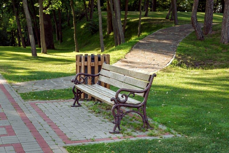 Un banc avec un siège en bois et repasser les jambes forgées photographie stock libre de droits