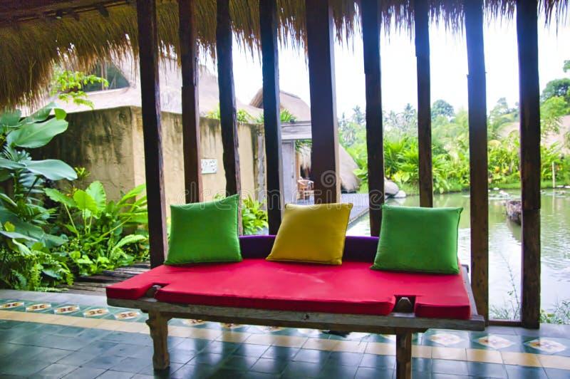 Un banc Balinese de style de Batavia de teakwood ? c?t? d'un lac Concept de luxe confortable de voyage photographie stock