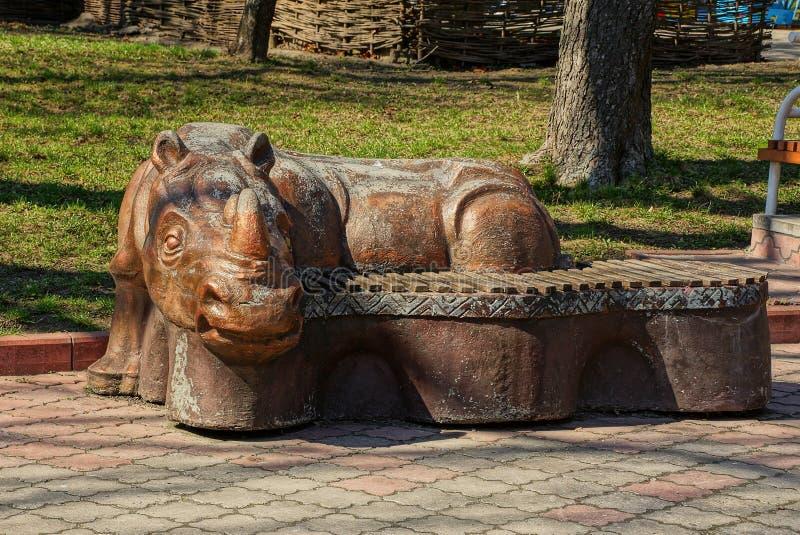 Un banc brun avec un chiffre de rhinocéros se tient sur le trottoir en parc images libres de droits