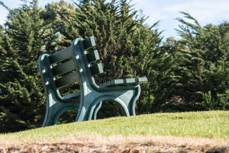 Un banc de parc vert se repose sur une colline herbeuse, inoccupée, un jour ensoleillé images libres de droits