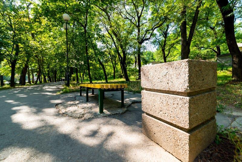 Un banc en bois jaune le soir d'été de parc au soleil Est tout près une poubelle concrète carrée photographie stock
