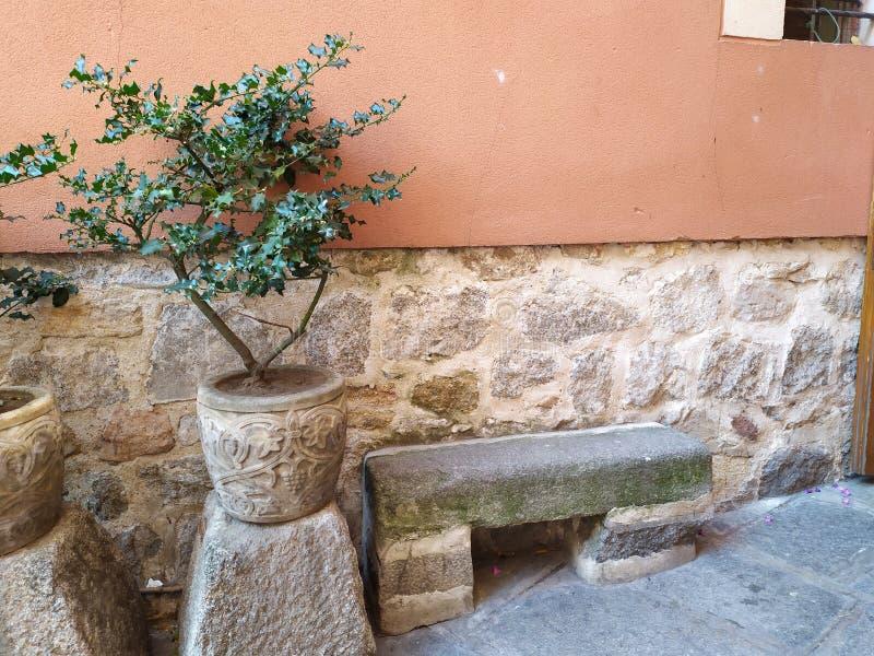 Un banc en pierre et un pot de fleurs dans une rue intéressante photos libres de droits