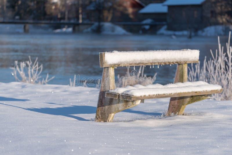 Un banc froid et congelé couvert dans la neige en Suède photographie stock