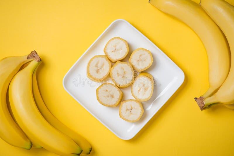 Un banch de plátanos y de un plátano cortado en un plato sobre el CCB amarillo fotografía de archivo