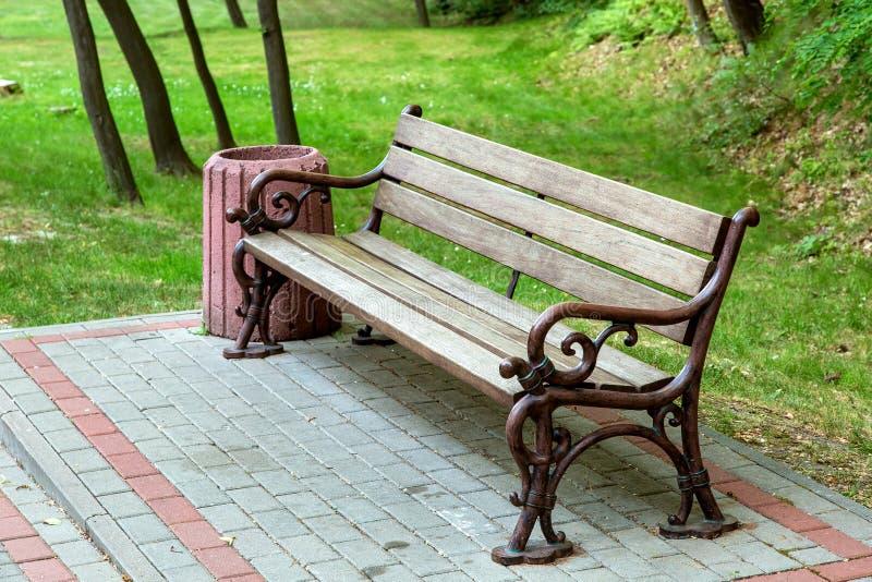 Un banco con un sedile di legno e rivestire di ferro le gambe forgiate immagine stock