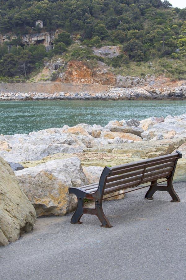 Un banco de madera vacío con vistas al mar Mediterráneo en la 'promenade' de la playa, Cinque Terre, Oporto Venere, Italia fotografía de archivo