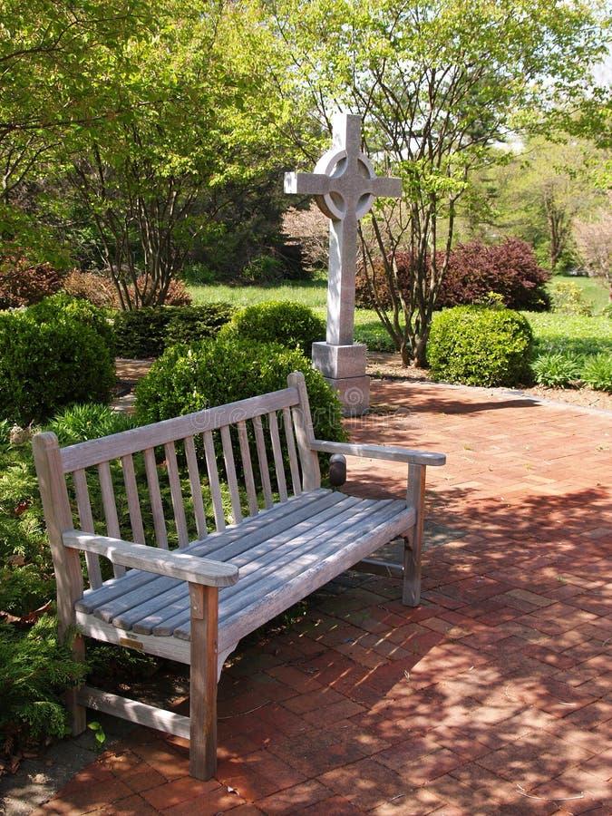 Un banco de madera vacío por un patio de la cruz y del ladrillo rojo foto de archivo