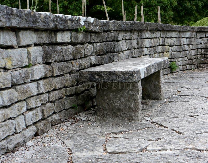 Un banco de piedra robusto colocado contra una pared de ladrillo de piedra Jardín botánico de Visby en Gotland, Suecia imágenes de archivo libres de regalías