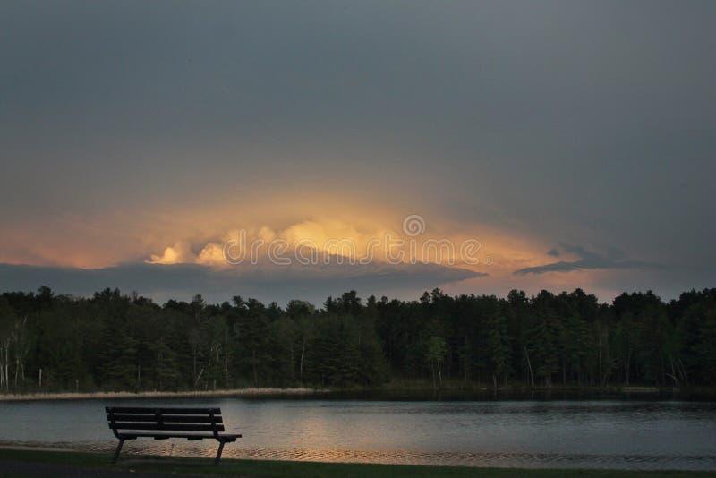 Un banco solitario en un lago en la puesta del sol fotografía de archivo