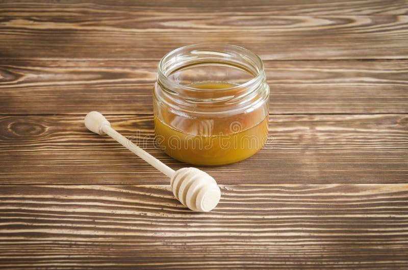 Un barattolo di miele e del bastone del miele fotografie stock libere da diritti