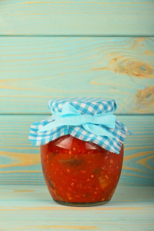 Un barattolo di vetro dell'insalata marinata del pepe a legno blu fotografia stock