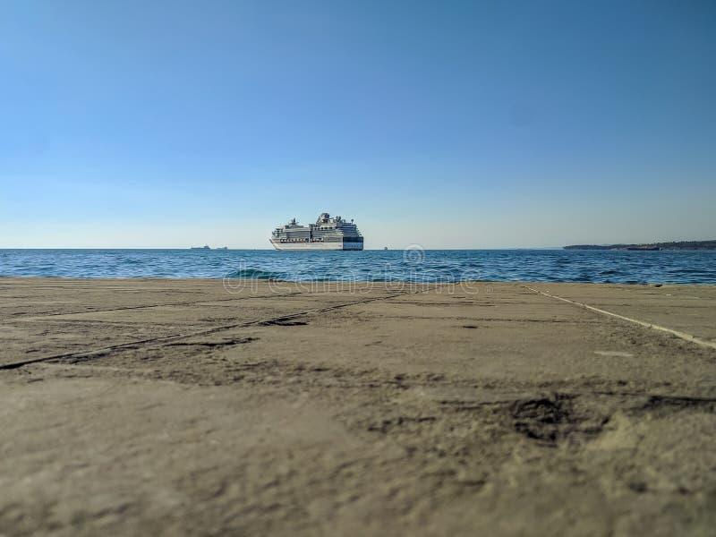 Un barco de cruceros grande está siguiendo a su destino a través del mar adriático por la tarde En la puesta del sol el trazador  foto de archivo