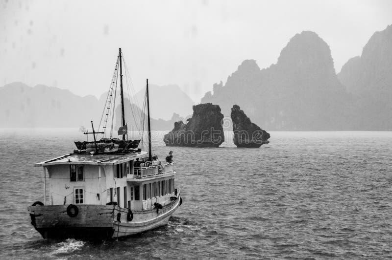 Un barco de los desperdicios navega en la bahía larga de la ha, Vietnam, con lluvia en el primero plano y niebla en la distancia imagen de archivo