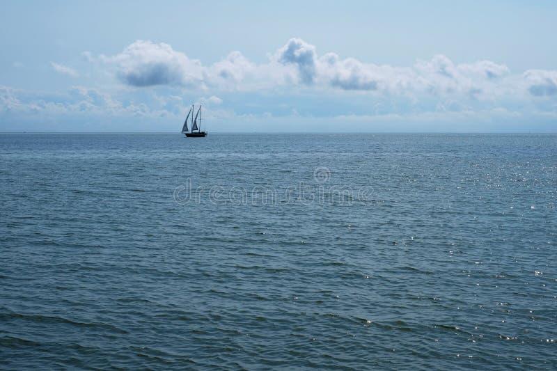Un barco de navegación en la línea del horizonte imagenes de archivo