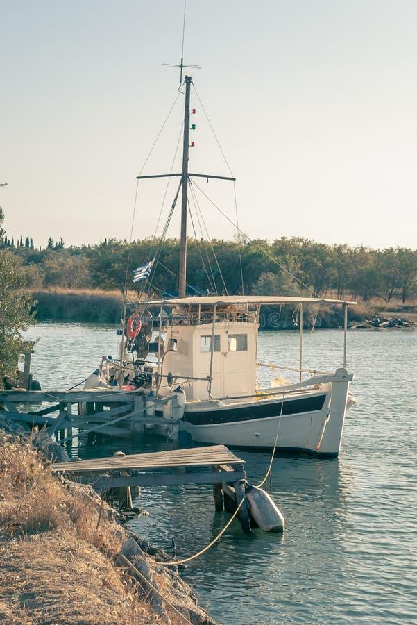Un barco de pesca atado a un pequeño embarcadero de madera fotografía de archivo libre de regalías