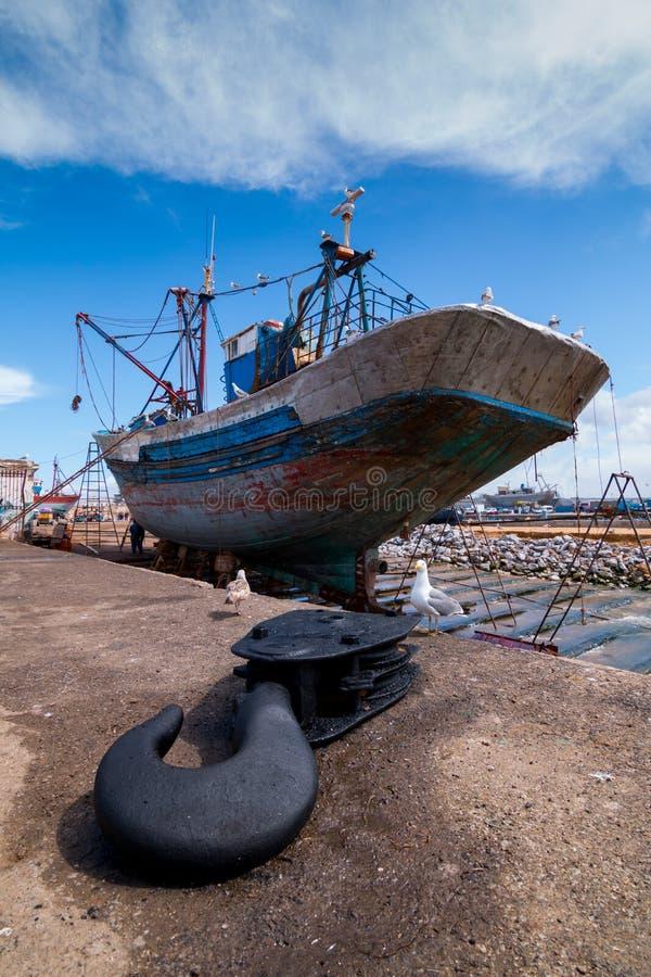 Un barco de pesca atracado en las esperas del muelle para una reparación completa con un gancho de barco en el primero plano fotografía de archivo