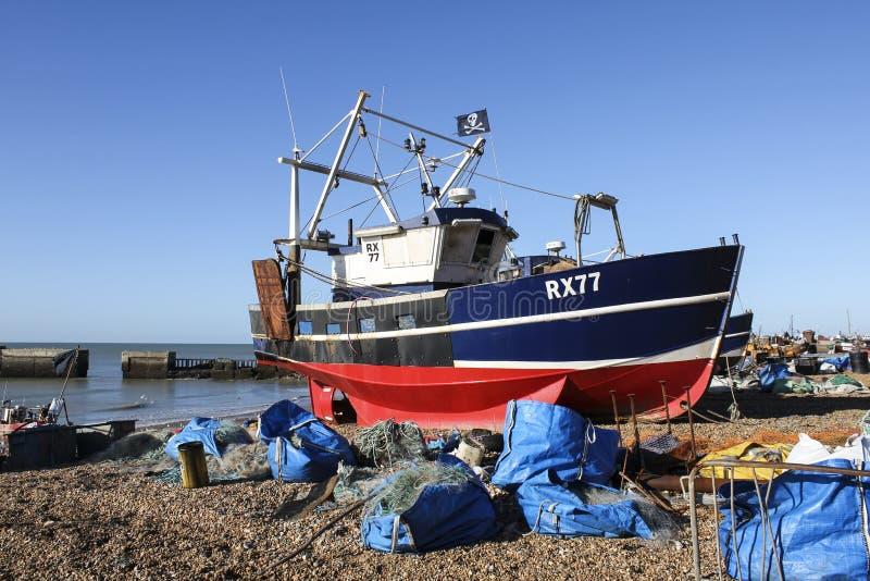 Un barco de pesca brillante-coloreado de Hastings onshore sobre el brazo del puerto foto de archivo