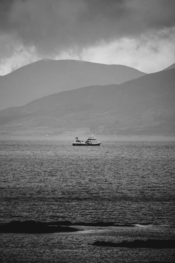 Un barco de pesca dirige hacia fuera al mar en clima tempestuoso Isla de Skye, imagen de archivo